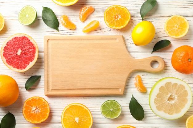 Zitrusfrüchte, blätter und brett auf holzhintergrund, draufsicht