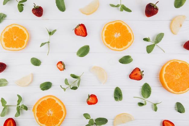 Zitrusfrüchte, blätter und erdbeeren auf dem blauen holztisch.