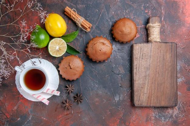 Zitrusfrüchte drei cupcakes zitrusfrüchte eine tasse tee das schneidebrett