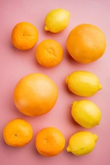 Zitrusfrüchte eingestellt, auf rosa strukturiertem sommerhintergrund, draufsicht flach