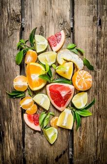Zitrusfrüchte - grapefruit, orange, mandarine, zitrone, limette in scheiben geschnitten und ganz mit blättern. auf holztisch. draufsicht