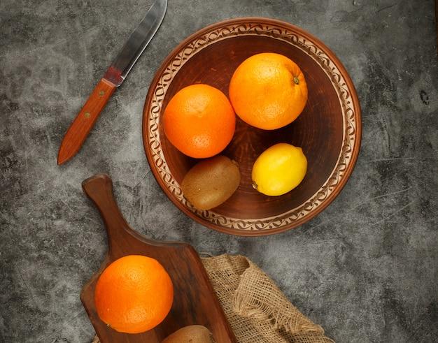 Zitrusfrüchte in einer keramikschale. draufsicht.