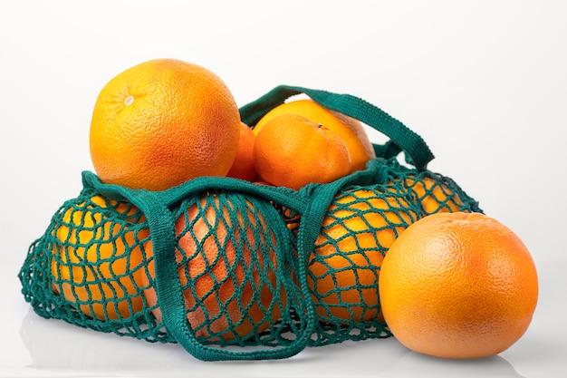 Zitrusfrüchte in grünem stringbeutel lokalisiert auf weißem hintergrund. orange, grapefruit, mandarine. ganze grapefruit oder orange separat. kein plastik.