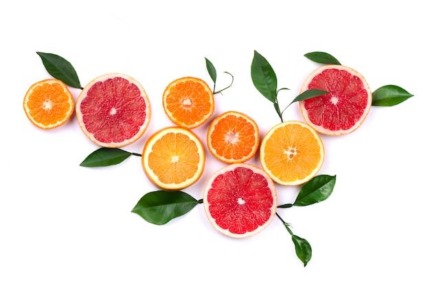 Zitrusfrüchte isoliert auf weiß. stücke von zitrone, rosa grapefruit und orange mit schnittpfad. draufsicht