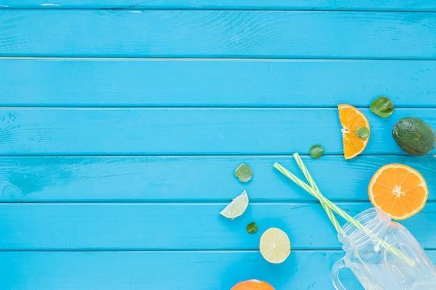 Zitrusfrüchte mit glas und strohen auf tabelle