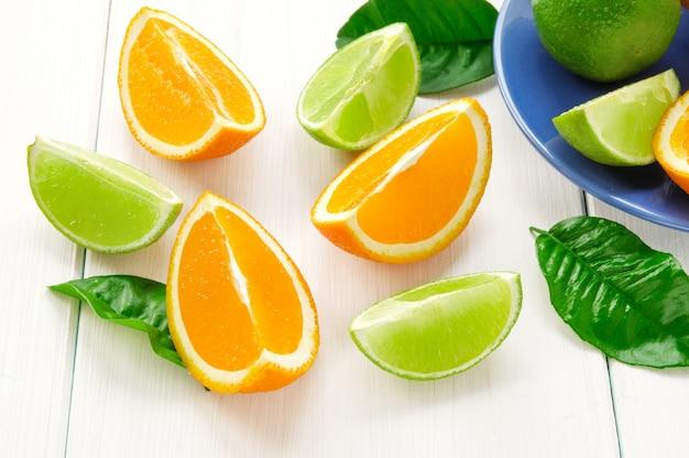 Zitrusfrüchte mit grünen blättern. orange, limettensegmente auf weißer holzoberfläche