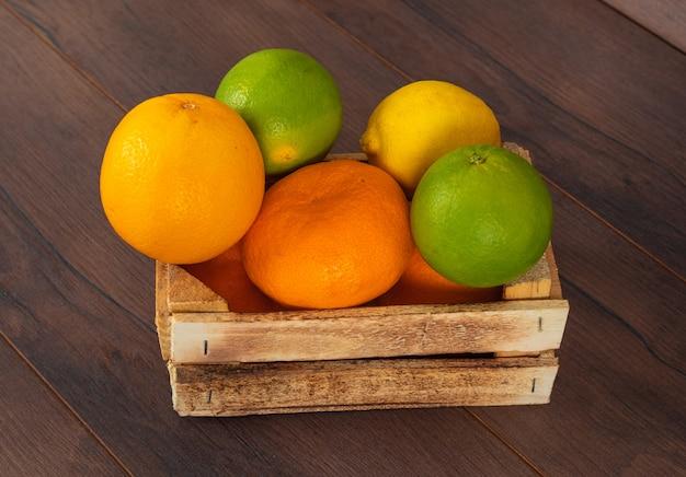 Zitrusfrüchte orange grüne und gelbe zitronenmandarine in der holzkiste auf braun
