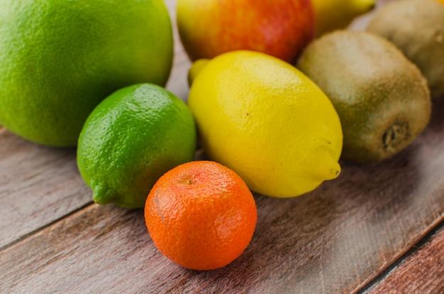 Zitrusfrüchte orange, zitrone, pampelmuse, mandarine, kalk auf einem hölzernen hintergrund