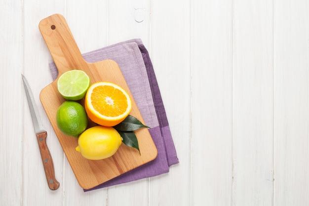 Zitrusfrüchte. orangen, limetten und zitronen. über holztischhintergrund mit kopienraum