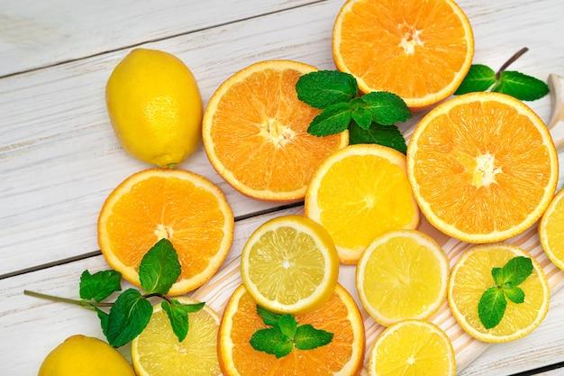 Zitrusfrüchte. orangen, zitronen und minze. geschnittene zitrusfrüchte auf einem hölzernen hintergrund.