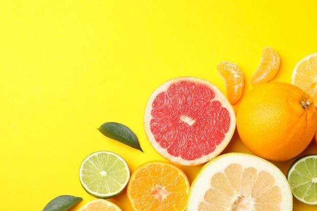 Zitrusfrüchte und blätter auf gelbem hintergrund, draufsicht