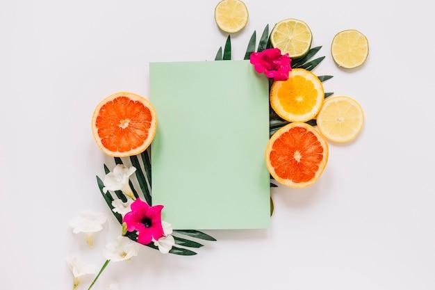 Zitrusfrüchte und blumen nahe papierblatt auf blatt