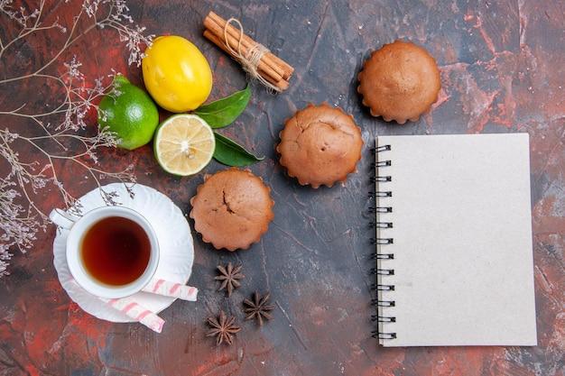 Zitrusfrüchte weißes notizbuch drei cupcakes zitrusfrüchte eine tasse tee