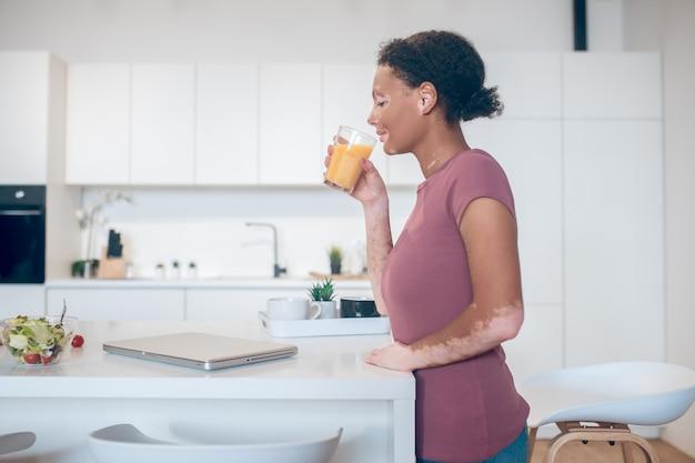 Zitrusgetränk. eine dunkelhäutige frau, die einen orangensaft trinkt
