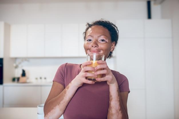 Zitrusgetränk. eine dunkelhäutige frau mit einem glas orangensaft