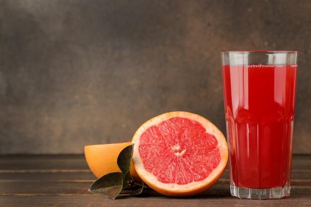 Zitrussäfte. grapefruitsaft in einem glas mit frischem obst auf einem braunen holztisch