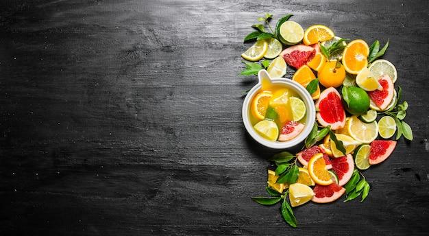 Zitrussaft aus zitrusfrüchten. grapefruit, orange, mandarine, zitrone, limette auf schwarzem holztisch. draufsicht