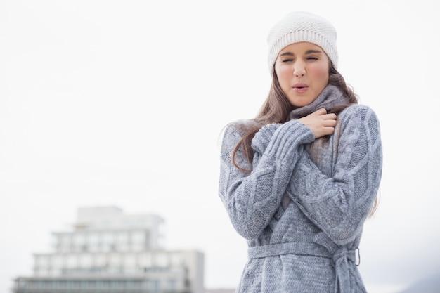 Zitternde hübsche frau mit winter kleidet auf der aufstellung