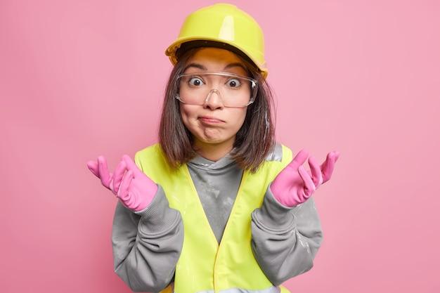 Zögernd verwirrt asiatische unternehmerin industriearbeiterin breitet handflächen seitwärts aus und sieht mit ahnungslosem ausdruck aus, weiß nicht, wovon sie in uniform auf der baustelle arbeiten soll
