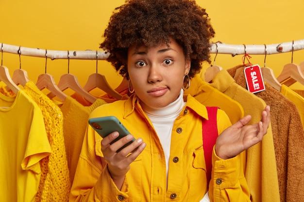 Zögernde afroamerikanische frau mit lockiger frisur, hebt die handfläche, wählt kleidung aus der neuen kollektion in einer boutique oder einem bekleidungsgeschäft aus und steht gegen kleidung auf lumpen