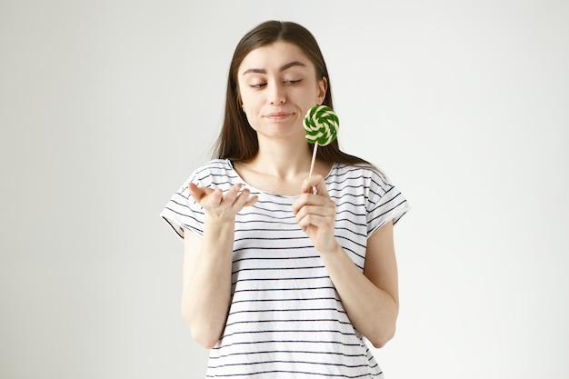 Zögernde brünette frau im gestreiften t-shirt macht unsichere geste, hält spiralförmig harte bonbons in der hand und spitzt lippen