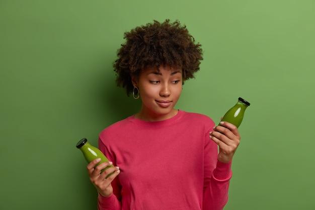 Zögernde frau mit afro-haaren betrachtet detox green smoothie in glasflasche, trinkt gesundes gemüsegetränk, führt fitness-lebensstil und richtige ernährung, konsumiert vegetarisches essen, das reich an vitaminen ist