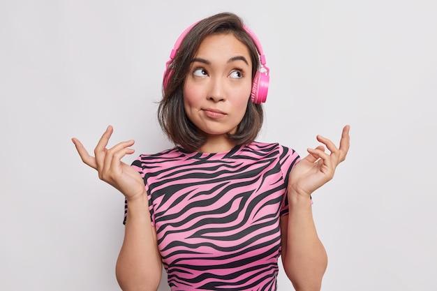Zögernde junge asiatische frau zuckt mit den schultern hat ahnungslosen ausdruck macht auserlesene tagträume, während das hören von musik ein lässiges gestreiftes t-shirt trägt, das über weißer wand isoliert ist.