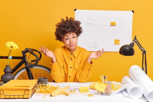 Zögernde junge dunkelhäutige afroamerikanische architektin posiert an einem gemütlichen arbeitsplatz, umgeben von papieren, sitzt am desktop