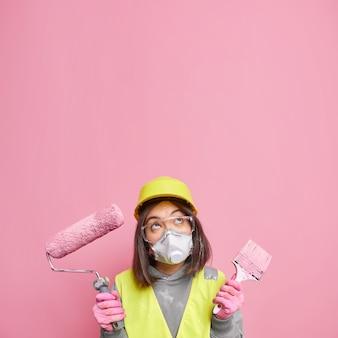 Zögernde junge professionelle asiatische dekorateurin hält malwerkzeuge und denkt über hausrenovierung nach, die sich oben konzentriert, trägt schutzhelm-atemschutzgerät und schutzbrille isoliert auf rosa wand