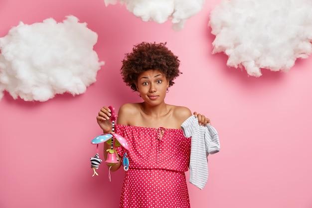 Zögernde lockige frau hält zwei gegenstände und notwendigkeiten für baby, hält kinderkleidung und handy, denkt, was besser für neugeborene zu kaufen ist, hat großen schwangeren bauch. schwangerschafts- und geburtskonzept