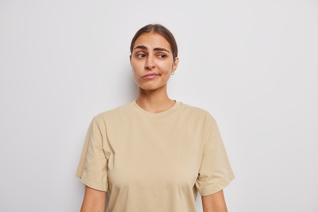Zögernde unzufriedene frau schürzt die lippen hat den unzufriedenen ausdruck in frage gestellt denkt an etwas, das in beigem t-shirt gekleidet ist, isoliert über weißer studiowand?