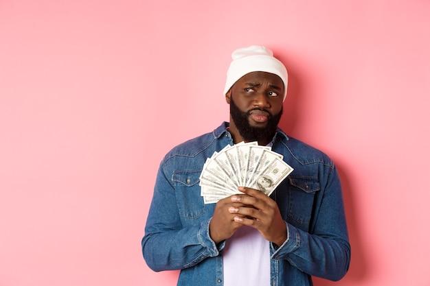 Zögernder afroamerikanischer mann, der geld hält, mit zweifeln und bedenken nach links schaut und vor rosafarbenem hintergrund steht.