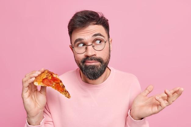 Zögernder bärtiger junger mann zuckt mit den schultern und hält leckere pizza, ohne sich dessen bewusst zu sein, sieht in freizeitkleidung ahnungslos weg