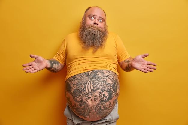 Zögernder dicker mann mit großem tätowiertem bauch, zuckt mit den schultern und sieht verwirrt aus, steht vor einem dilemma, trifft eine ernsthafte entscheidung, trägt ein untergroßes gelbes t-shirt und posiert drinnen. menschen und zweifel konzept