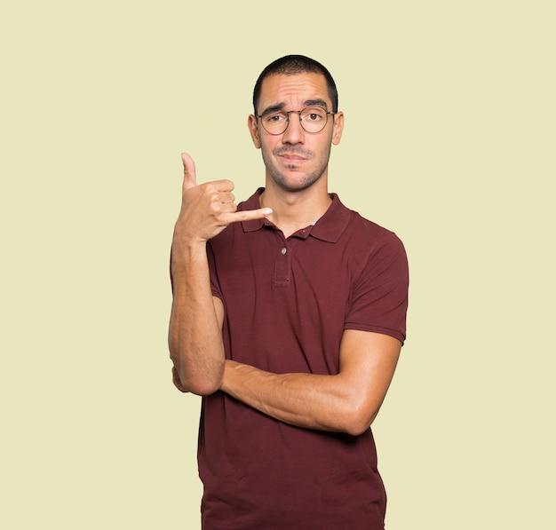 Zögernder junger mann macht eine geste des anrufens mit der hand