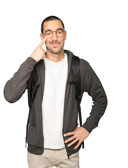 Zögernder student, der eine geste macht, vorsichtig zu sein, wobei seine hand auf sein auge zeigt