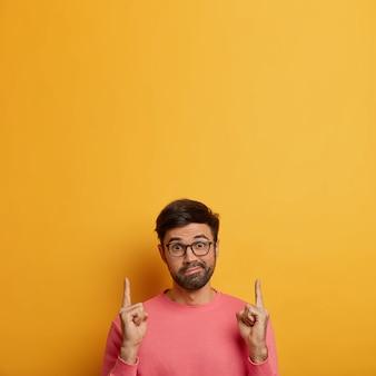 Zögernder überraschter mann zeigt mit verwirrtem gesichtsausdruck nach oben, zeigt auf leerzeichen, hat zweifel und fragt nach ihrer meinung, trifft verwirrte wahl, trägt eine brille und einen freizeitpullover, gelbe wand