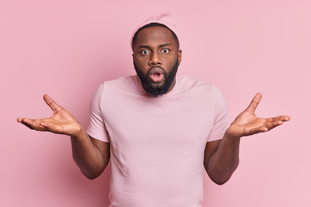 Zögernder verwirrter schockierter schwarzer mann breitet palmen aus, verwirrt von schwieriger situation sieht überrascht aus und ahnungslos trägt hut-t-shirt isoliert über rosa wand