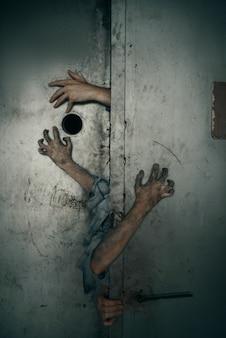 Zombie-hände ragen aus der aufzugstür, tödliche jagd. horror in der stadt, gruselige krabbeltiere, weltuntergangsapokalypse, blutige monster