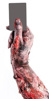 Zombie-hand, die ein kreditkartenmodell hält, werbung oder werbung für das halloween-thema verwendet.