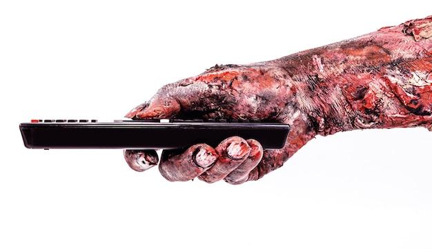 Zombie-hand, die eine fernsehfernbedienung hält, isolierte weiße oberfläche, halloween-thema.