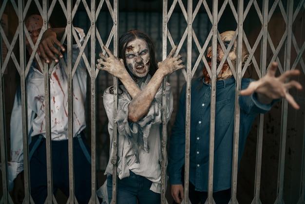Zombie hinter den gittern des aufzugs, todesfalle, tödliche jagd. horror in der stadt, gruselige krabbeltiere, weltuntergangsapokalypse, blutige monster