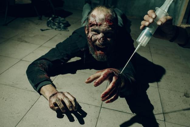 Zombie und doktor mit heilimpfspritze in der hand. halloween-konzept.