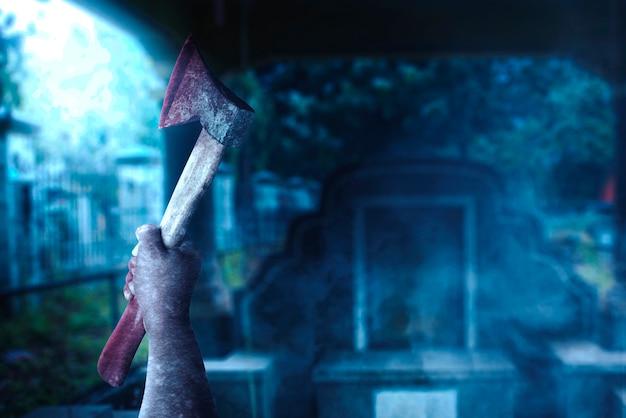 Zombiehände mit wunde, die eine axt auf dem friedhof halten