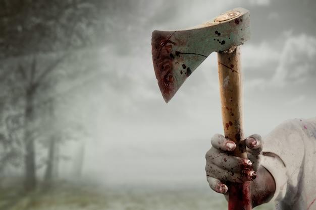 Zombiehände mit wunde, die eine axt in einem verwunschenen wald halten