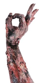 Zombiehand in ok geste, positives handgestenmonster, untote, weiße oberfläche.