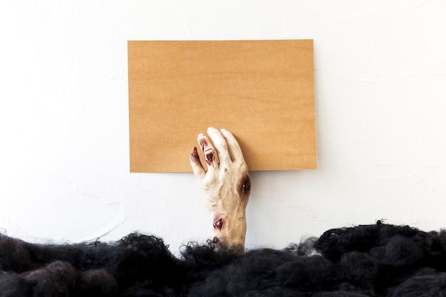 Zombiehand mit papierblatt