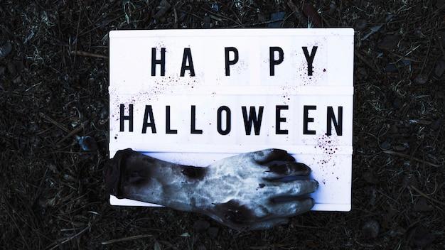 Zombiehand mit schild auf waldboden