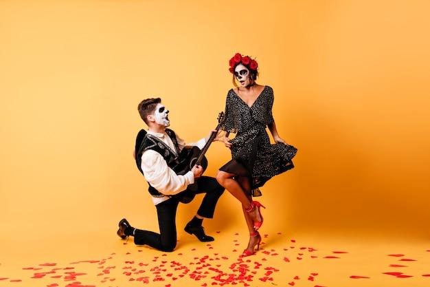 Zombiemann spielt serenade. innenfoto des kerls mit muerte make-up, das mit gitarre neben frau im schwarzen kleid aufwirft.