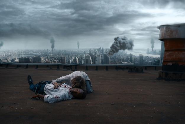 Zombiepaar auf dem dach eines verlassenen gebäudes, tödliche verfolgungsjagd. horror in der stadt, gruseliger krabbelangriff, apokalypse